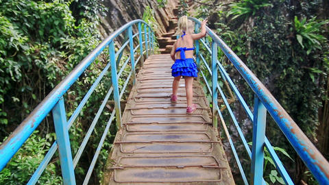 Little Blond Girl Walks along Bridge over Canyon Smiles in Park Footage