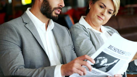 Businessman holding newspaper and interacting with woman Live Action