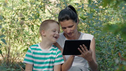 Young Mother And Son Using Tablet PC In The Forest Footage