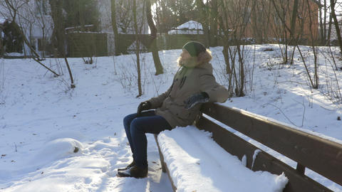Man sitting on a bench with snow in winter Footage