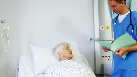Doctor interacting with a patient on medical bed Footage