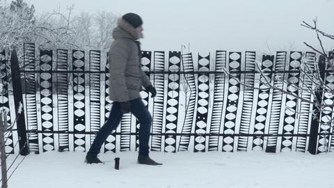 Man Walks Along Modern Fence Footage