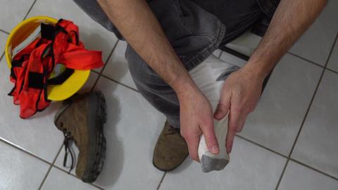Man Massages Foot Workboot Off Overhead Footage