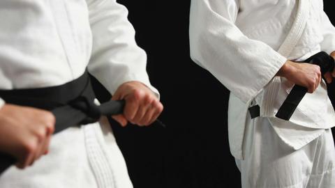 Men in black belt standing against black background Footage