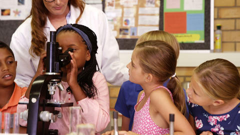 Teacher assisting school kids with experiment in laboratory Live Action
