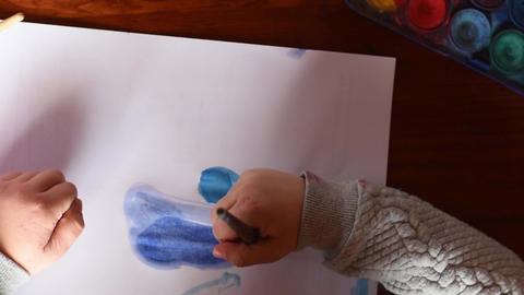 Top view of young girl painting on a paper sheet with a watercolor brush Live Action