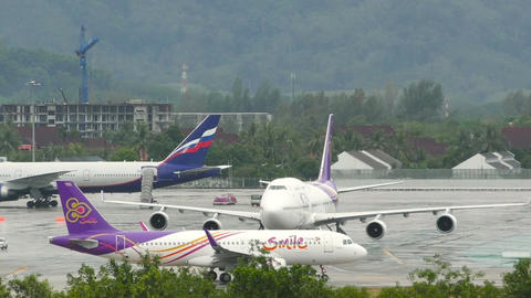 Airplane taxis on airfield against Boeing 747 standing with tow machine on it's  Footage