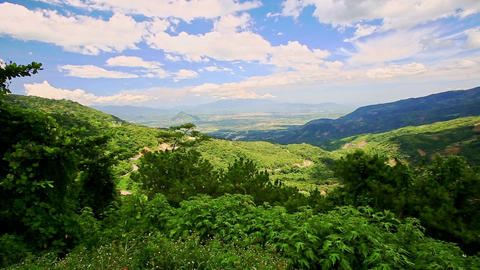 Hand Points to Green Valley among Hills Blue Sky White Clouds Footage