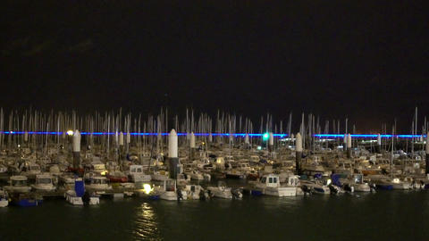 Yachts and small boats moored at marina, night view of vessels in large harbor Footage