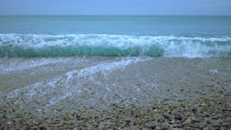 Foamy ocean wave rolling ashore in slowmotion, pebble beach under foggy sky Footage