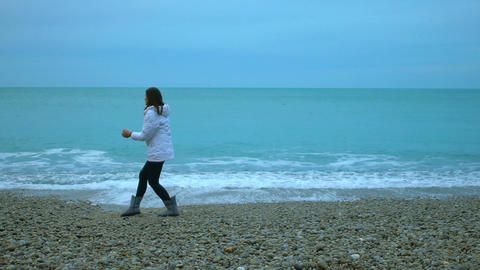 Young woman throwing pebbles into ocean, foamy waves splashing ashore in slow-mo Footage