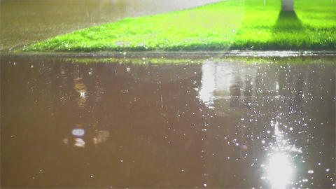 Raindrops splashing on city pavement, summer storm, slippery road conditions Footage