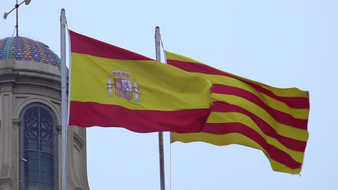 Spanish and Catalan flags with coat of arms fluttering in wind against blue sky Footage