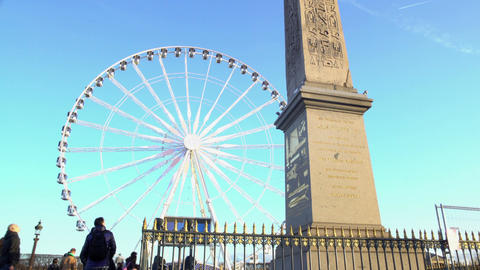 Tourists looking at high Egyptian Luxor Obelisk, huge observation wheel in Paris ビデオ