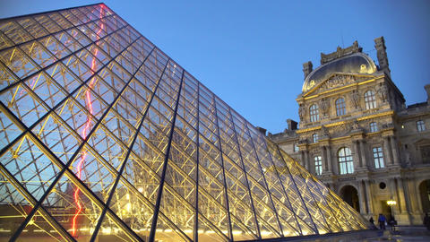 Night view of illuminated Louvre Palace with glass pyramid, famous Paris sights Footage
