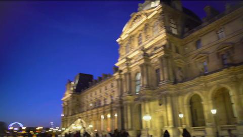 Panorama of majestic Louvre Palace building illuminated at night, many tourists Footage