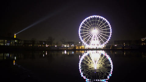 Night Paris view, illuminated Eiffel Tower, Ferris wheel reflection in water Footage