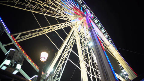 Merry night at amusement park, colorful illuminated giant Ferris wheel rotating Footage