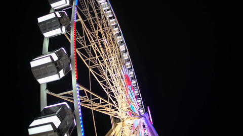 Side view of huge Ferris wheel rotating at amusement park under dark night sky Footage