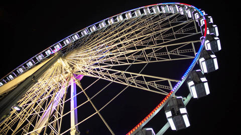 Ferris wheel at amusement park, colorful illuminated construction moving slowly Footage