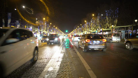 Many cars driving night city road, trees decorated with bright sparkling lights Footage