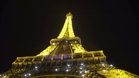 Illuminated Eiffel Tower sparkling at night, tourist attraction, view from below Live Action