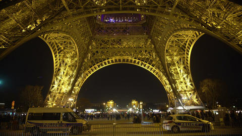 Many travellers walking around Eiffel Tower in Paris at night, police on duty Footage