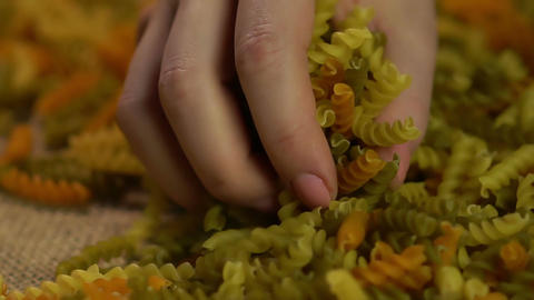 Female hand taking handful of macaroni, Italian kitchen, healthy food production Footage