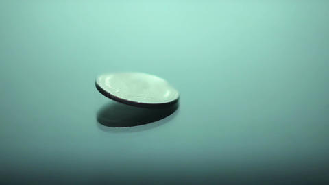 Silver coin falling on glass table in slow-motion, heads and tails, fortune Live Action