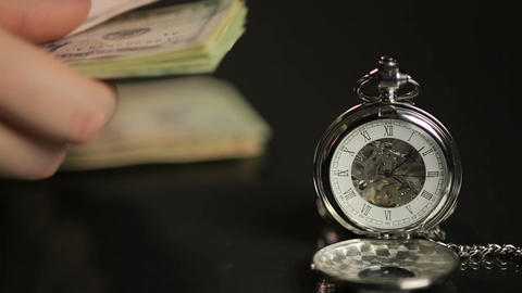 Closeup of silver pocket watch, hands counting paper money, time flies fast Footage