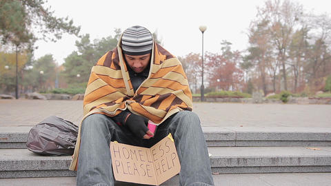 Sad male beggar sitting alone in park, warming up with old blanket, man coughing Live Action