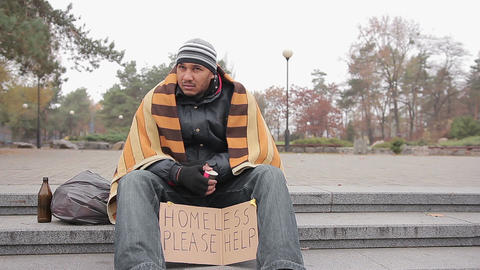 Homeless man in shabby clothes sitting in city park with sign asking for help Live Action
