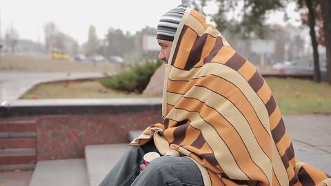 Lonely homeless man covered with shabby blanket feeling cold, asking for money Live Action