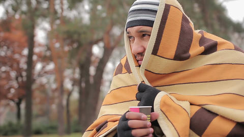 Poor man with sad face hiding from cold in shabby blanket, warming with hot tea Live Action