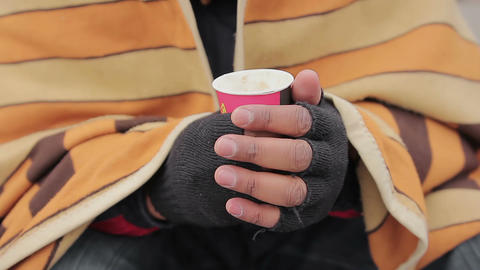 Needy person's hands holding warm drink in paper cup, closeup. Poverty issue Live Action