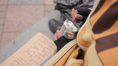 Socially vulnerable homeless person eating canned food in street, poverty issue Live Action