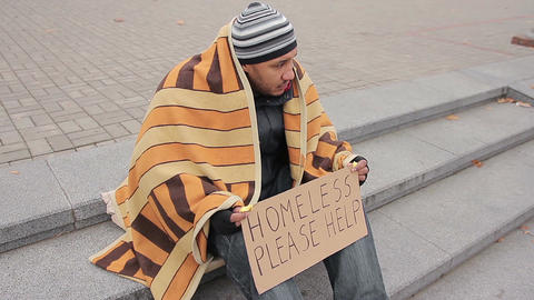 Miserable beggar shaking from cold in street with help sign, hoping for charity Live Action
