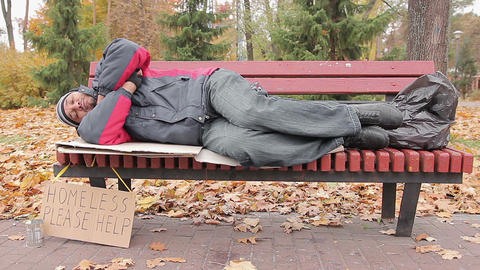 Needy male sleeping on bench in autumn park, homeless man waiting for help Live Action