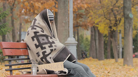 Lonely poor person sitting on bench, warming up with old blanket, man starving Footage