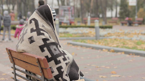 Mentally ill person hiding under blanket, happy people walking in autumn park Footage