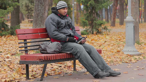 Drunk man sleeping on bench in park with bottle in hand, alcohol use disorder Footage