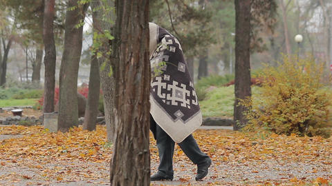 Lonely poor man limping in park, strange man covered with blanked needs help Footage