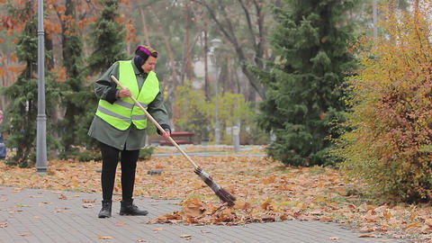 Senior woman cleaning city park, stops to have rest, looking at beautiful autumn Footage