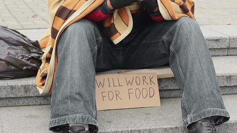 Man in park with ready to work for food sign, homeless begging, poverty, sadness Footage