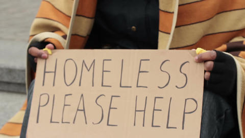 Adult man holding homeless please help sign, poverty, social vulnerability Live Action