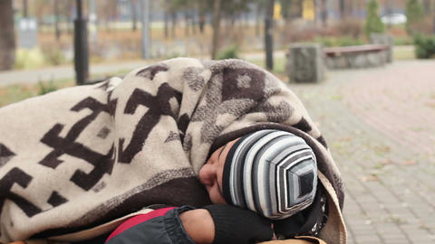 Frozen man lying on the bench in park, wrapping himself in blanket, poverty Footage
