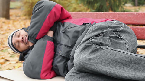 Vagabond in jacket and jeans sleeping on bench, trying to keep warm, poverty Footage