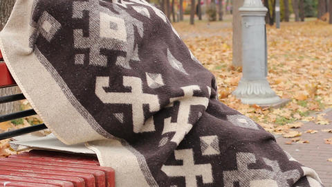Lonely poor man wrapped in blanket sitting on bench in park, thinking about life Footage