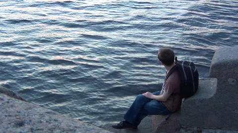 Boy sitting lonely by a river Footage