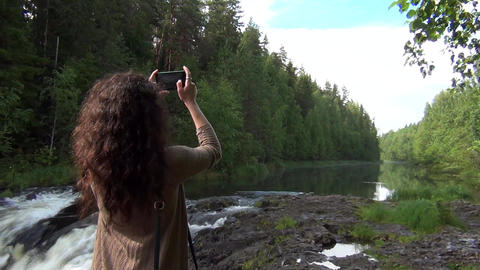 Woman taking photos of a river with smartphone Footage